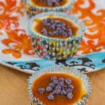 Rolo Cheesecake Cups lined up on a wood board and colorful plate
