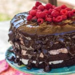 Triple Chocolate Layer Cake with raspberries on top sitting on a blue and green cake stand with a pink linen in the background