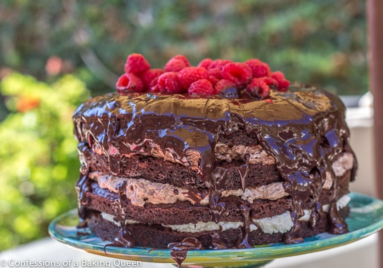 Triple Chocolate Layer Cake with raspberries on top on a blue cake plate