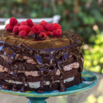 Triple Chocolate Layer Cake served on a blue cake stand outside