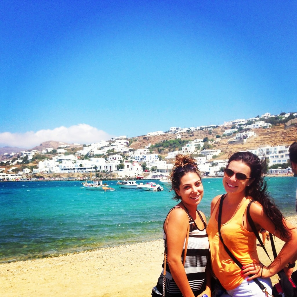 two girls in mykonos standing in front of the ocean and boats