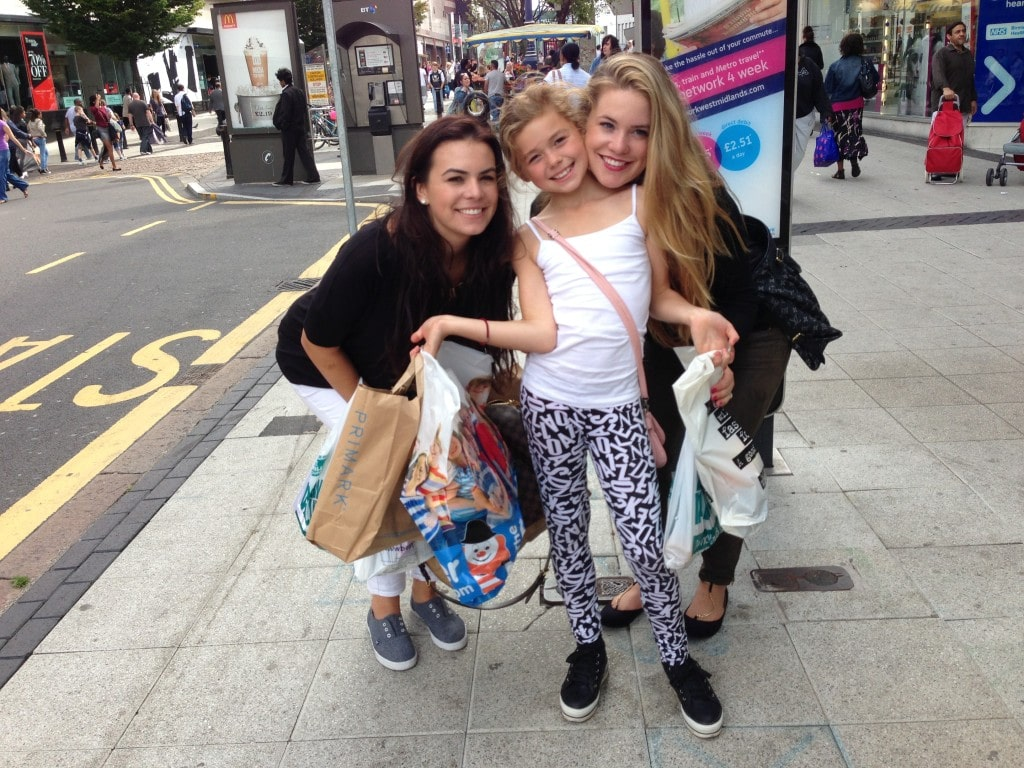 two older girls smiling with a younger girl with lots of shopping bags in a shopping center