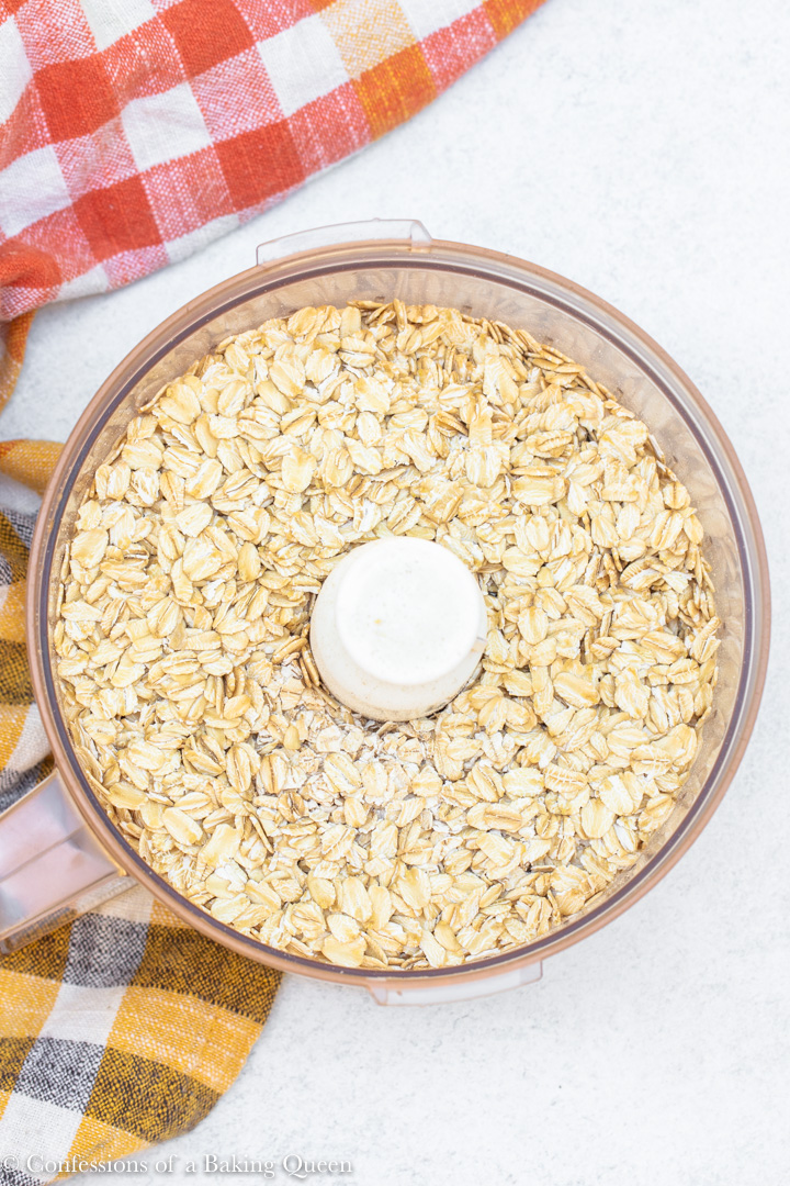 oats added to a food processor bowl before blending for an oat flour pumpkin bread recipe