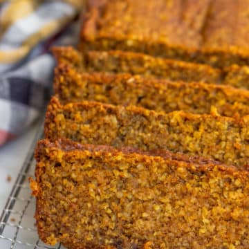 oat flour pumpkin bread sliced on a wire rack on a white background with an orange, yellow, and white linen
