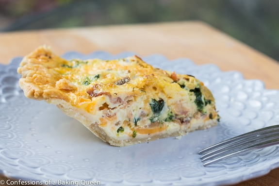 Bacon, Onion, Spinach Quiche side view on a purple plate with fork