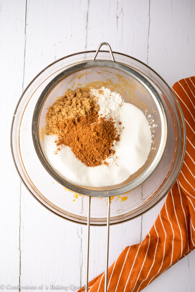 dry ingredients in a metal sieve over bowl of wet ingredients for a pumpkin bread recipe on a wood surface with an orange linen