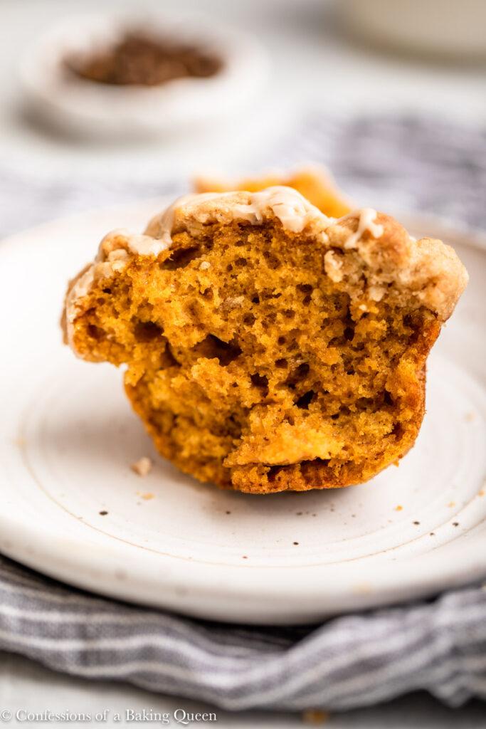 half eaten pumpkin muffin on a white plate on a blue linen on a light grey surface