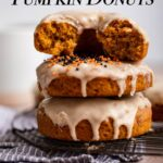 stack of pumpkin cake donuts on a black cooling rack on top of a blue striped towel