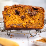pumpkin nutella bread slices on a wire rack on a white surface with a wooden knife and small bowl of spices