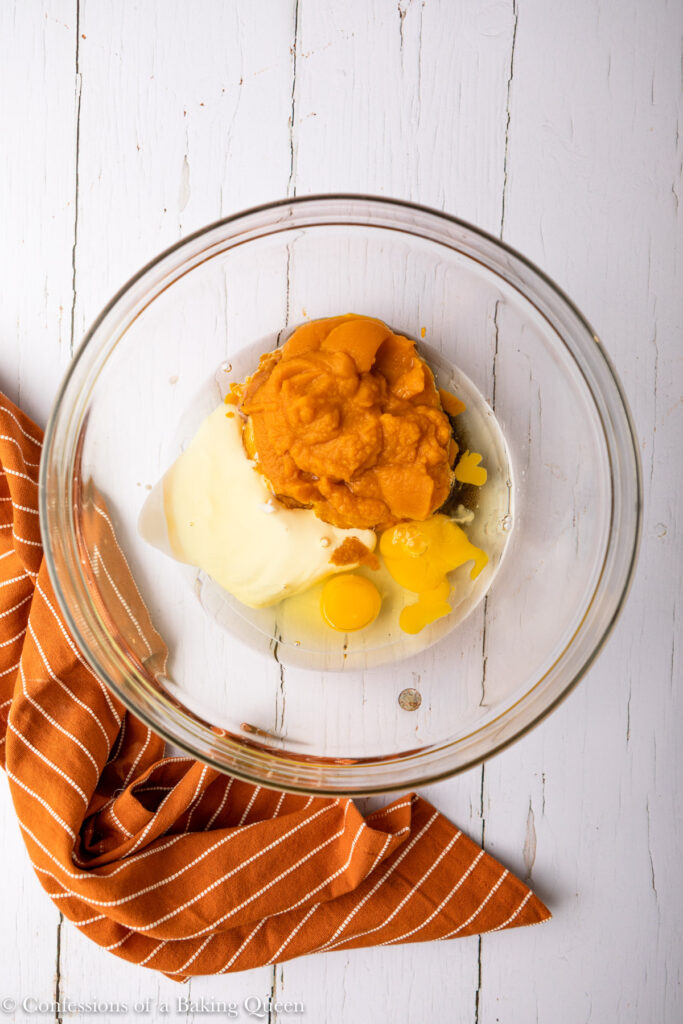 pumpkin puree, eggs, yogurt, vanilla, and oil in a large glass bowl on a white wood surface with an orange linen