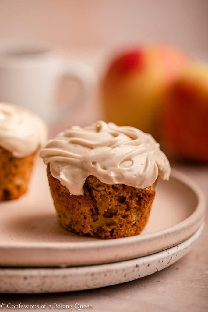 apple cupcake with maple frosting on a stack of plates with a cup of coffee and apples in the background on a light brown surface