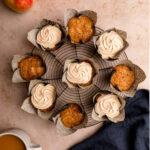 apple cupcakes with maple frosting on a wire rack on a light brown surface with a navy linen and apples and cup of coffee