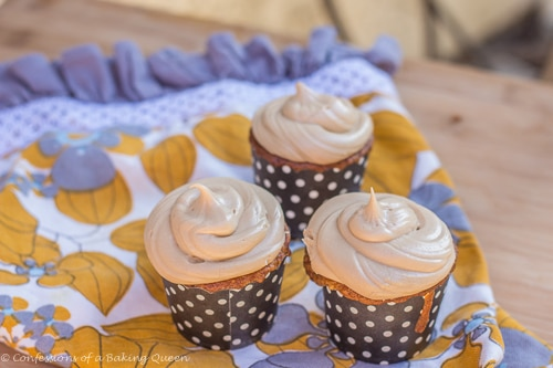 Apple Cupcakes Maple Cream Cheese Frosting served on a yellow grey and white tea towel on a wood surface