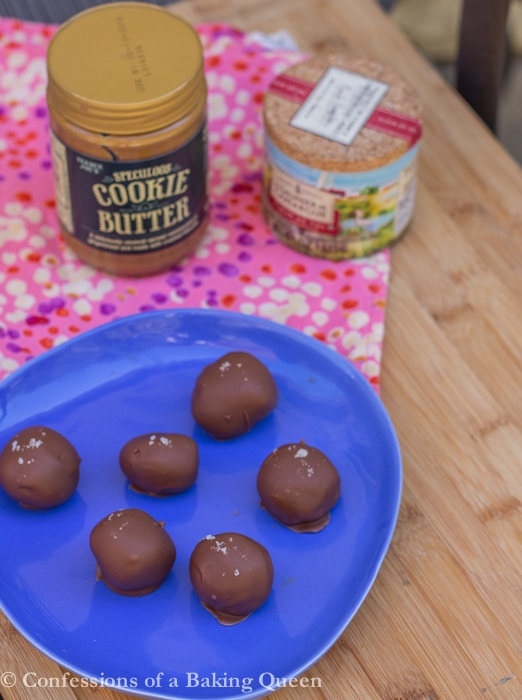 Cookie Butter Sea Salt Truffles served on a blue plate with cookie butter and fluer de sel in the background all on a wood board with a pink linen