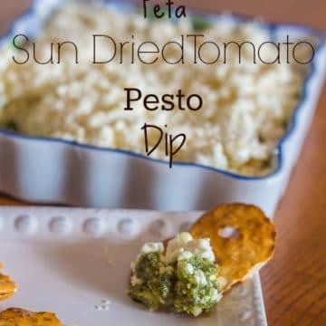 pretzel crisp and Feta Pesto Sun-dried Tomato Dip in the background on a wood board