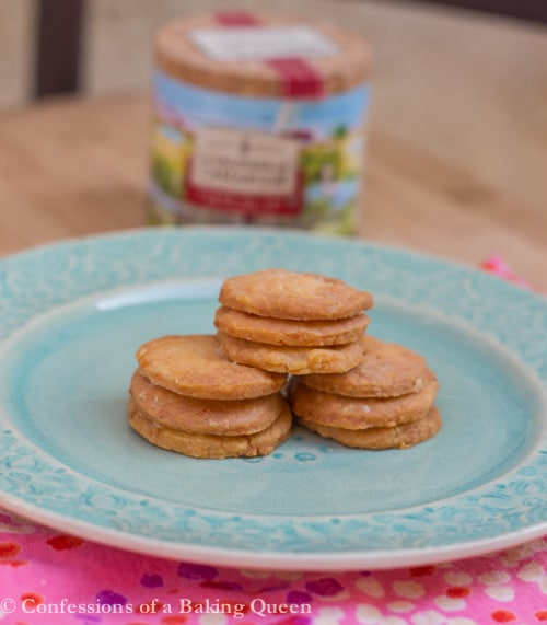 Homemade Cheese Crackers stacked on a light blue plate on top of a pink linen on a wood board