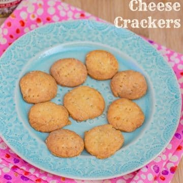 Homemade Cheese Crackers on a light blue plate on top of a pink linen on a wood board