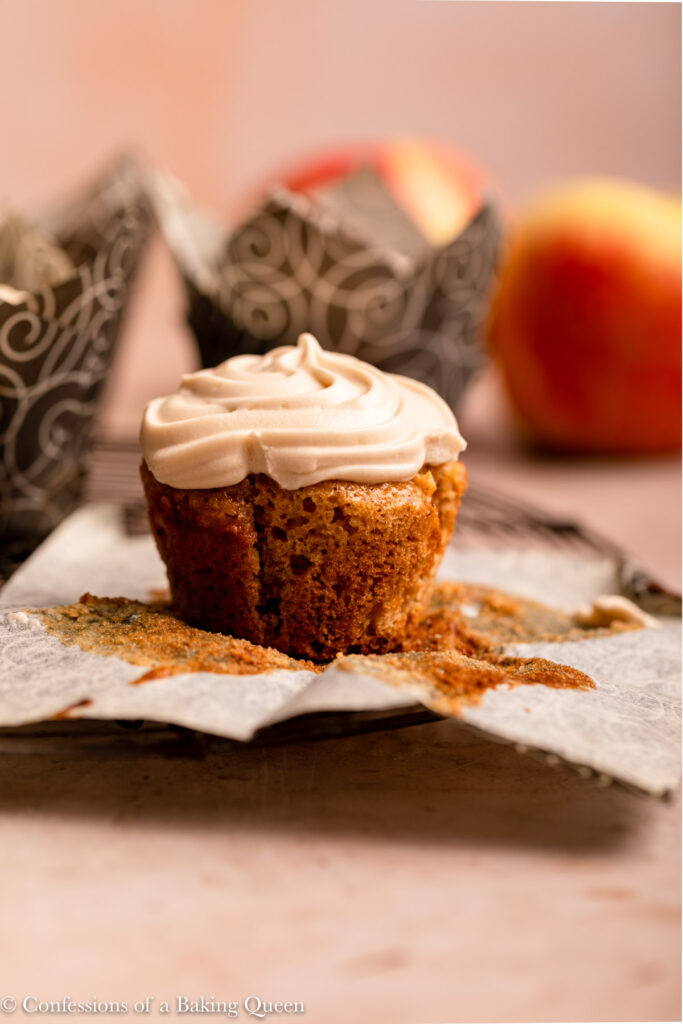 unwrapped apple cupcake on a wire rack with more cupcakes and apples in the background on a light brown surface