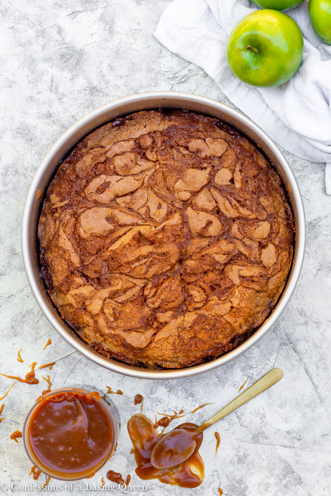salted caramel upside down apple cake on a grey background with apples in the corner and