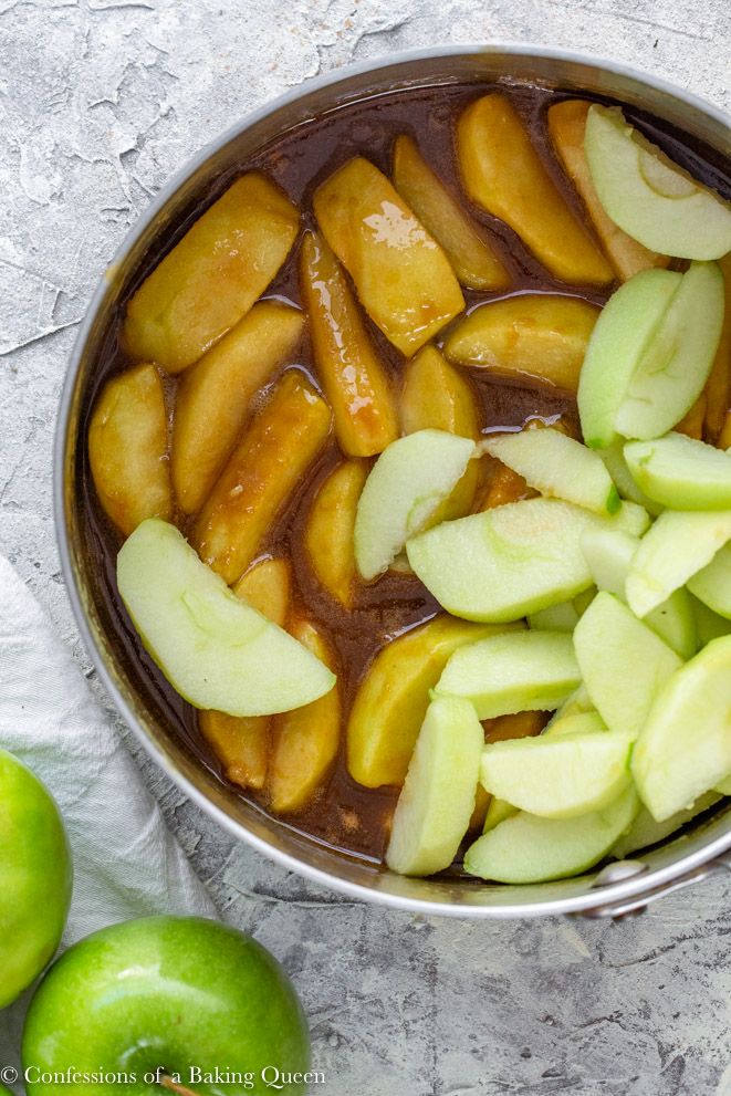 apple slices added to cooked apples sliced in a caramel sauce inside a large pot