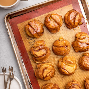 apple monkey bread muffins on a silpat lined sheet pan next to a cup of coffee and stack of plates and forks