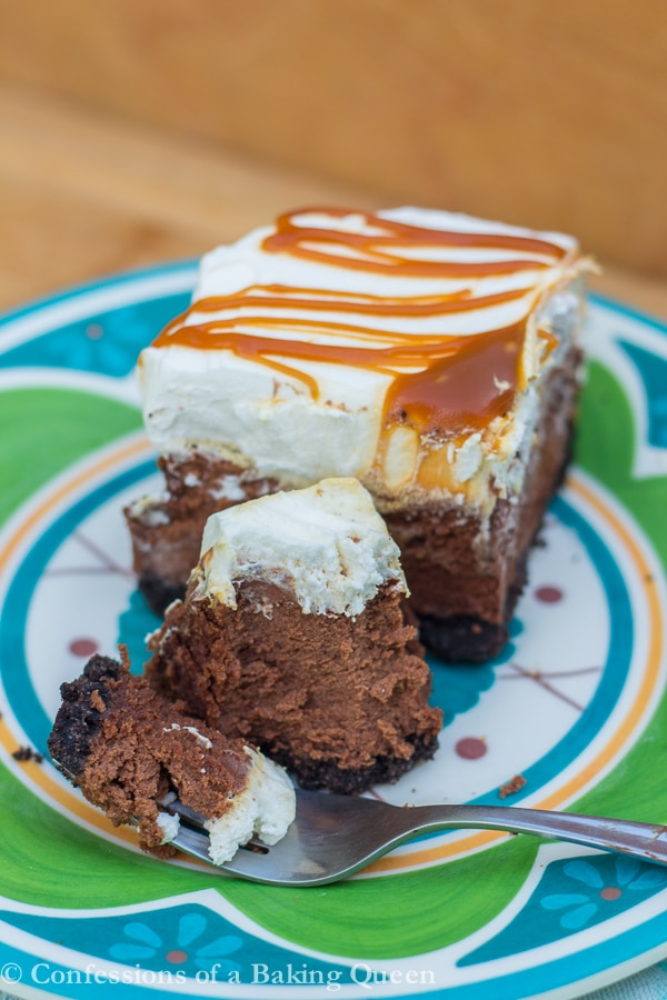 Salted Caramel Chocolate Cheesecake Bars with a fork taking a bite out on a blue and green plate