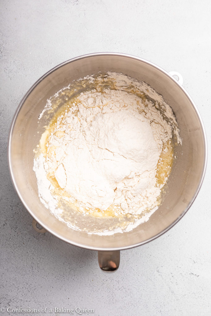 flour added to wet ingredients for an enriched dough recipe in a metal bowl