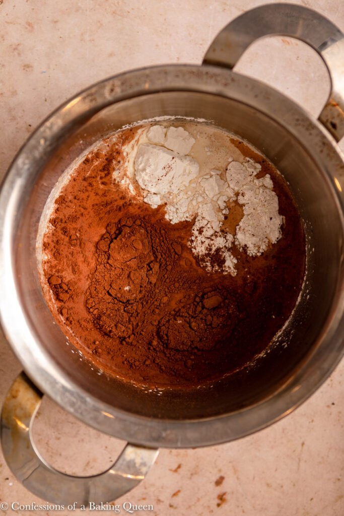 ingredients for chocolate tart in a metal pot on a light brown surface