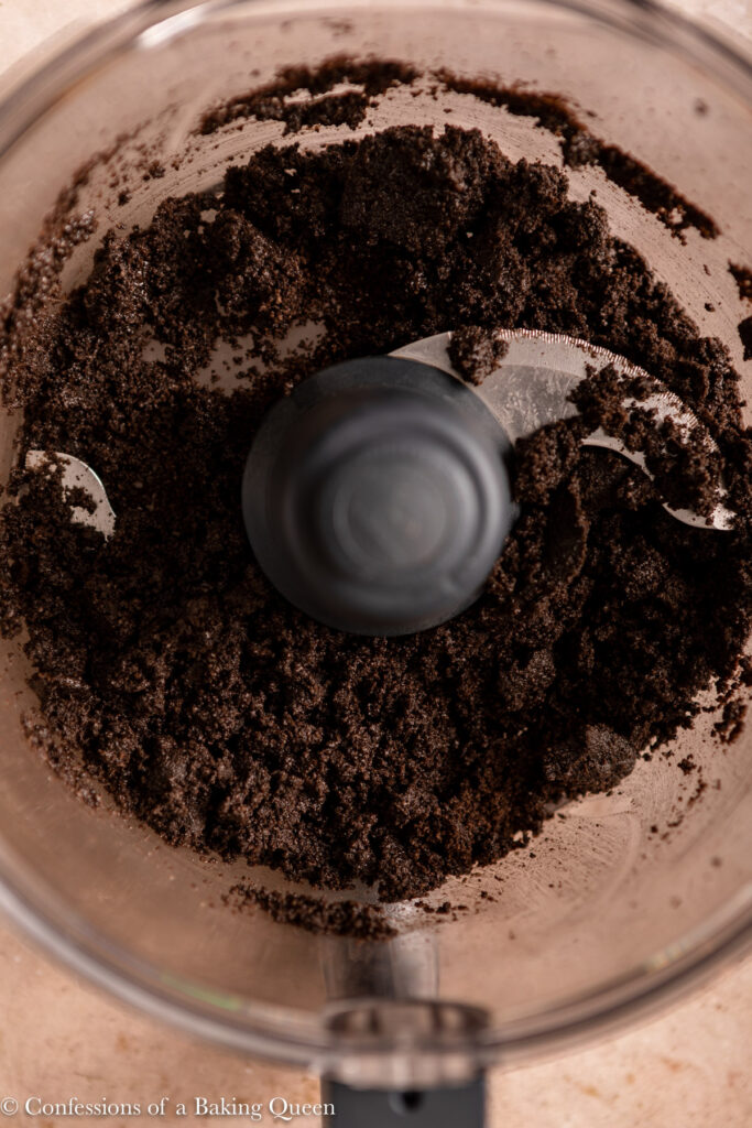 oreo crust crumbs up close in a food processor on a light brown surface