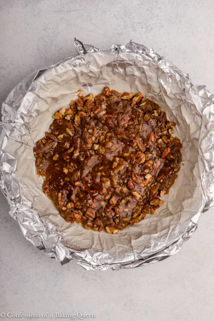 pecan topping added to the bottom of a foil lined pie dish