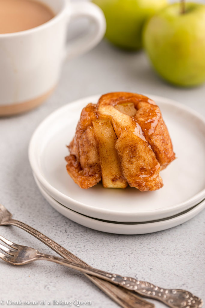 apple monkey bread muffin on a white plate next to a cup of coffee
