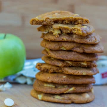 Salted Caramel Apple White Chocolate Cookies stacked on top of each other on a wood board next to an apple