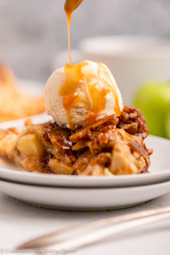 spoon drizzling caramel on top of salted caramel upside down apple pie with ice cream on a white plate