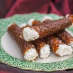 brandy snaps on top of each other on a white plate