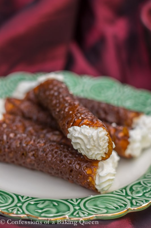 Brandy Snaps on top of each other on white plate with green rim on top of a red linen