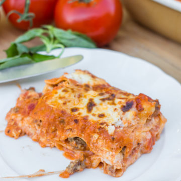Rosa Lasagna on a white plate with tomatoes in background on a wood board