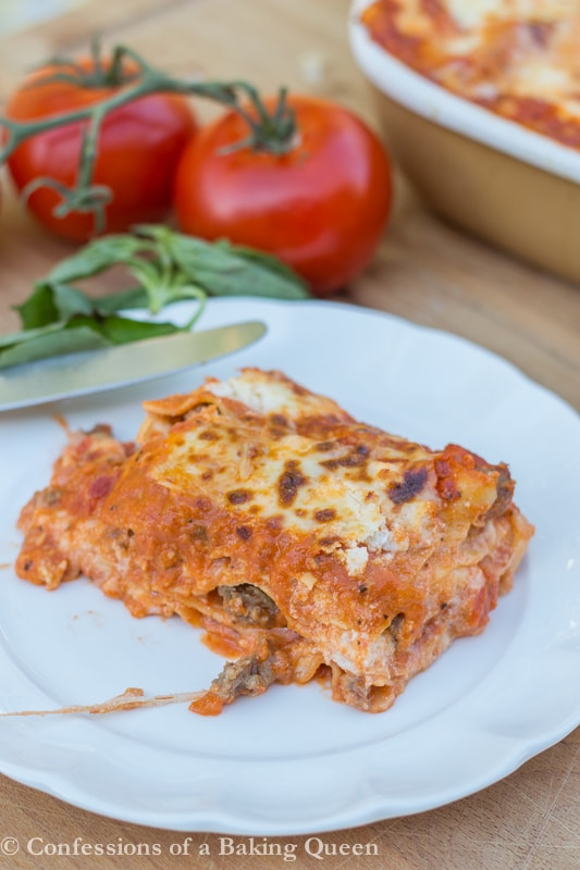 Rosa Lasagna on a white plate with tomatoes in background