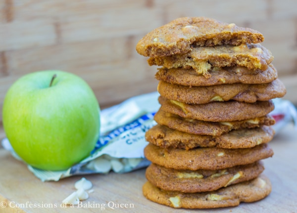 Salted Caramel Apple White Chocolate Cookies stacked with apple and white chocolate chip bag in the background