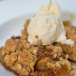 salted caramel apple crisp served in a white dish with ice cream on top