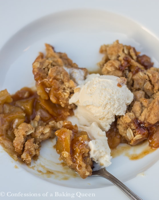 Caramel Apple Crisp baked and served in a white dish served with ice cream and spoon taking a bite