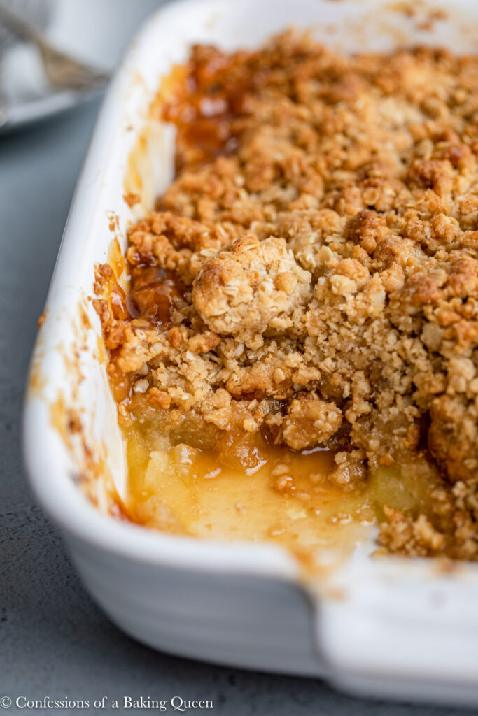 close up of apple crisp in a white ceramic dish