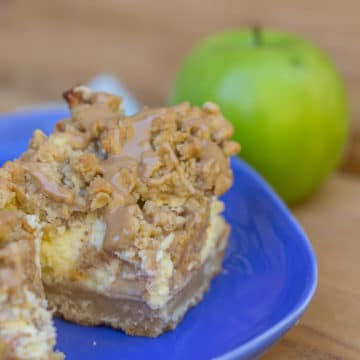 Maple Apple Cheesecake Bars on a blue plate with a green apple in the background on a wood background
