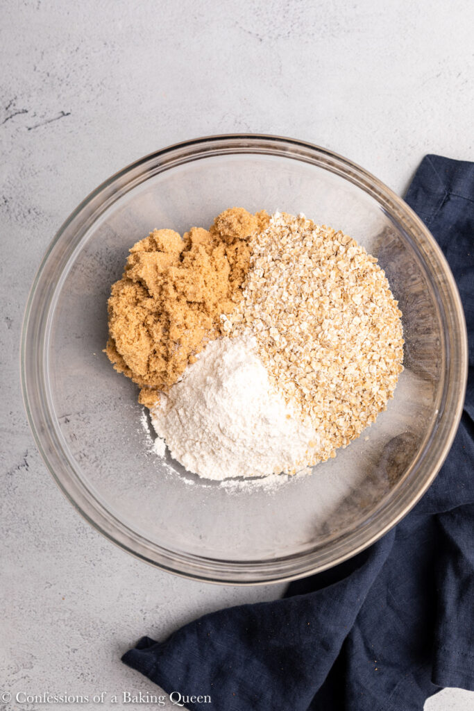 oats, flour, and brown sugar in a large glass bowl on a grey surface with a navy blue linen