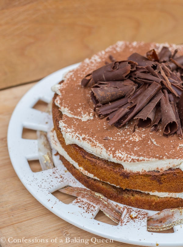 tiramisu cake on a white plate with a wood background