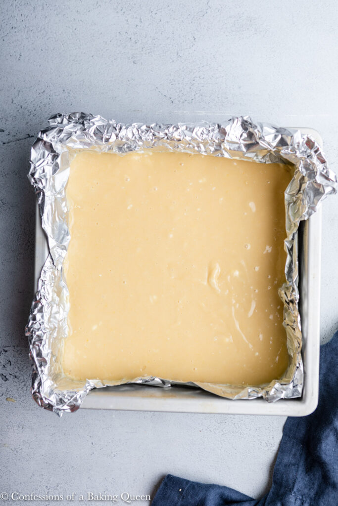 brown butter cake bars in a foil lined baking pan before baking on a grey surface with a blue linen