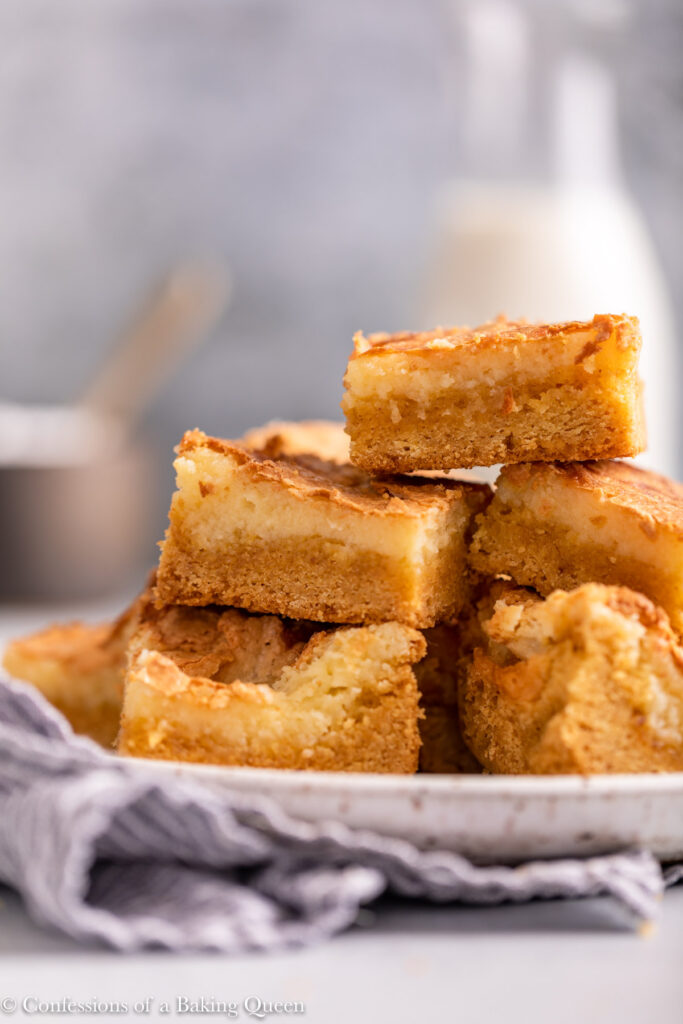 plate full of brown butter gooey cake bars on top of a white and blue linen on a light grey surface