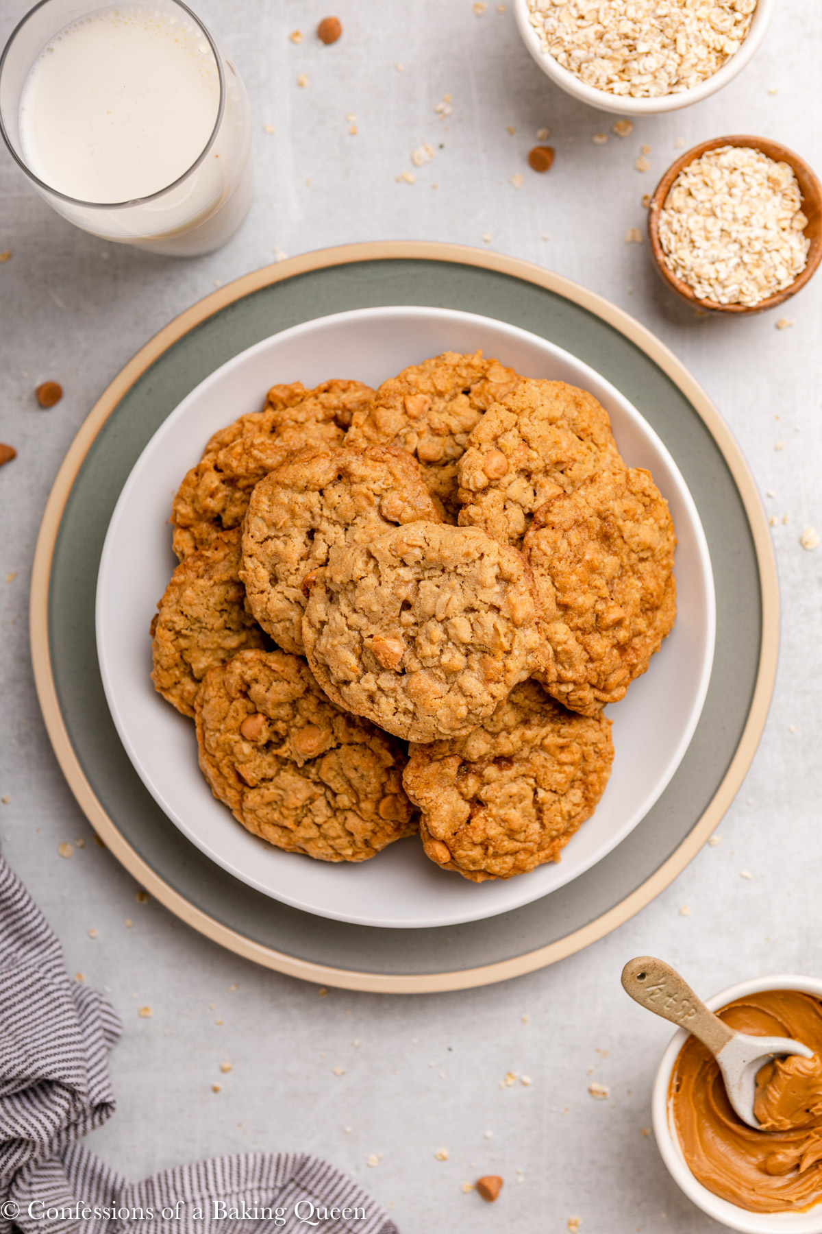 cookie butter oatmeal butterscotch cookies on a plate next to a glass of milk and small cup of oats