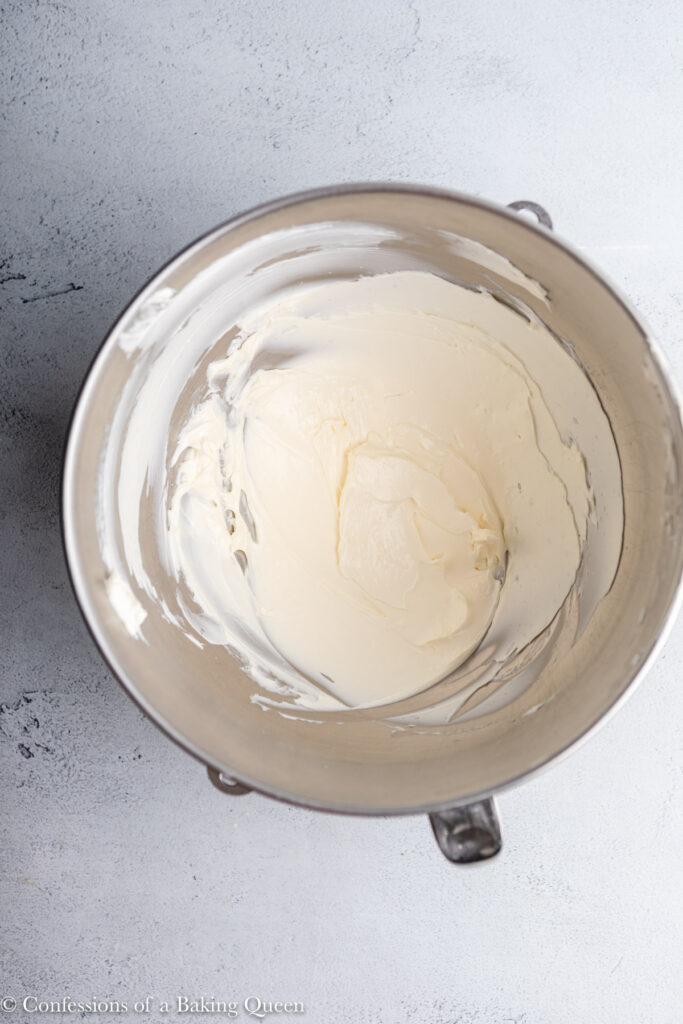 cream cheese whipped in a metal mixing bowl on a grey surface
