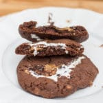 Chocolate Toffee Cookies Stuffed with Marshmallow Creme & Cookie Butter broken in half on top of a full cookie on a white plate with a wood background