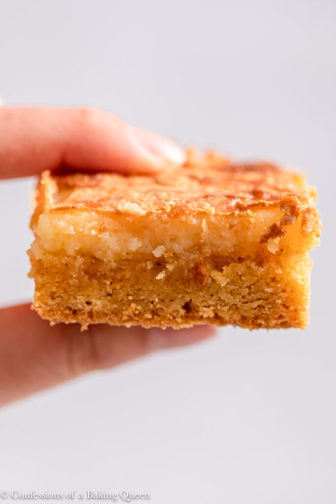 up close of hand holding a ooey gooey butter cake baron a light grey surface
